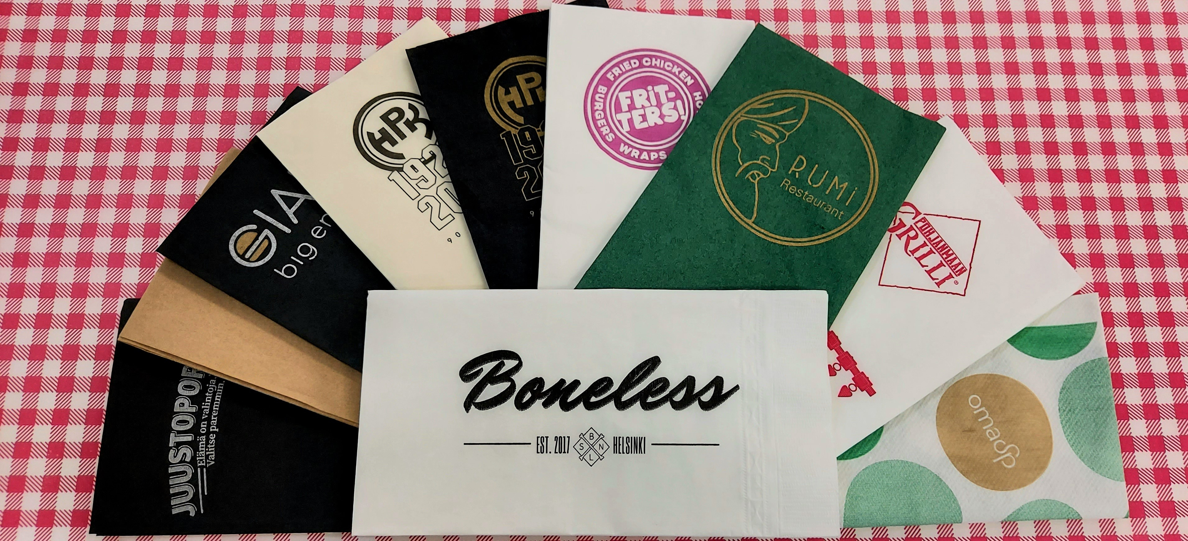 Selection of logoprinted serviettes on top of pepita printed food paper